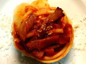 Bucatini all'amatriciana serviti arrotolati in tuile di parmigiano guarnito con guanciale croccante