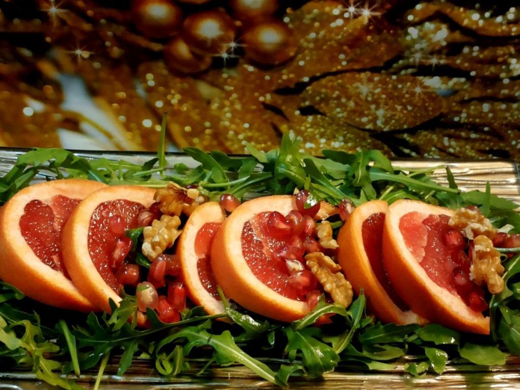 Insalata con rucola, pompelmo rosa, melograna e noci condita con vincotto primitivo. Nella foto presentata su un vassoio