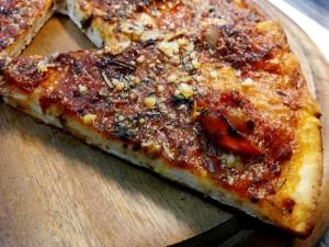 Pizza veloce con yogurt greco e senza lievitazione condita con pomodoro aglio ed aromi