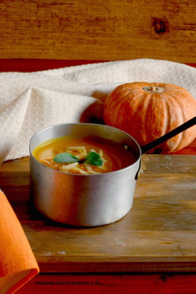 Vellutata di zucca e mandorle gluten free e senza lattosio presentata in un vecchio pentolino di rame adagiato su un tagliere di legno con la zucca arancione sullo sfondo