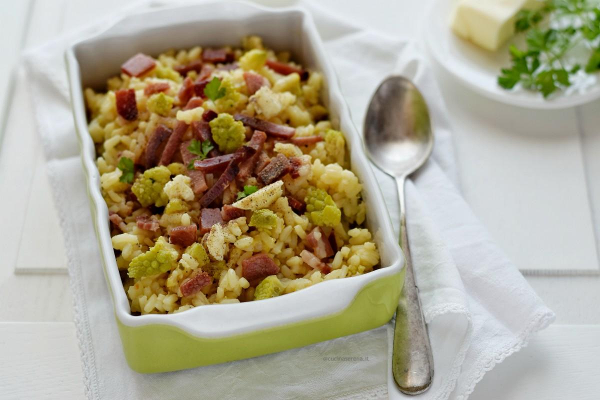 Riso al forno con verdure e speck, nella foto presentato in una terrina verde con interno bianco che risalta i colori della ricetta.