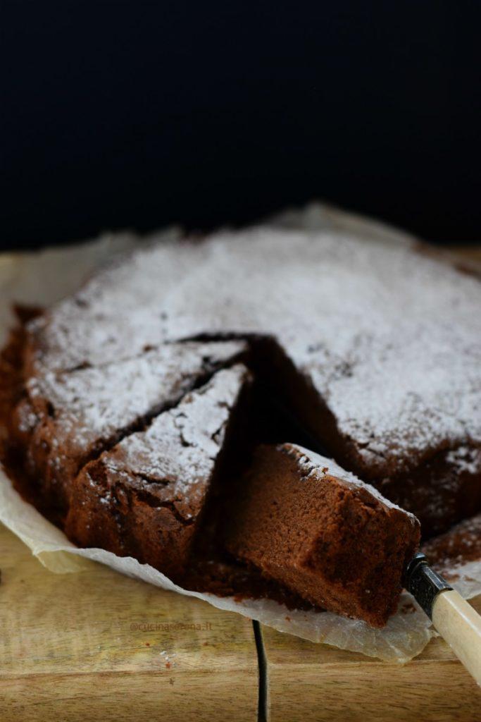 torta tenerine è un dolce al cioccolato fondente. Nella foto è adagiato su carta forno, ricoperto di zucchero a velo e tagliato a fette