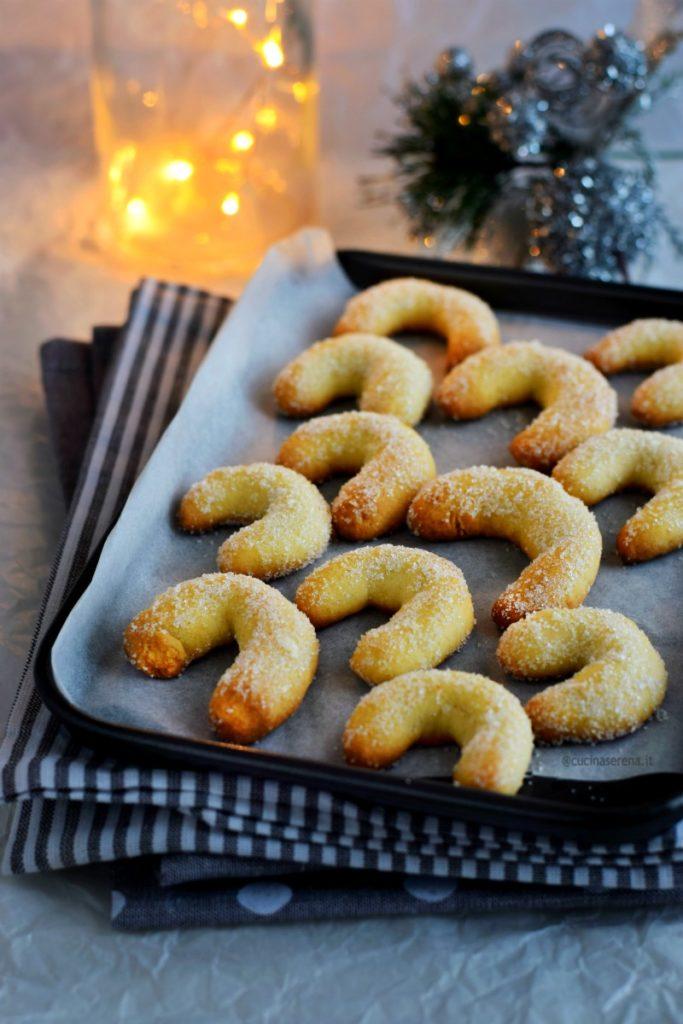 vanillikipferl biscotti alla vaniglia a forma di mezzaluna  messi su una teglia ricoperta di carta forno adagiata su canovacci a righe bianco e grigio con dietro lucine e decorazioni di natale