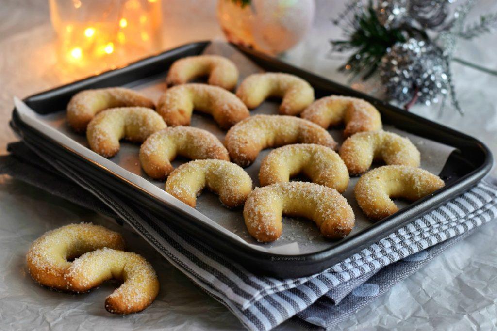 biscotti vanillekipferl a forma di mezzaluna ricoperti di zucchero adagiati su una teglia da forno posta su strofinacci color grigio sullo sfondo lucine di natale  e palline di natale