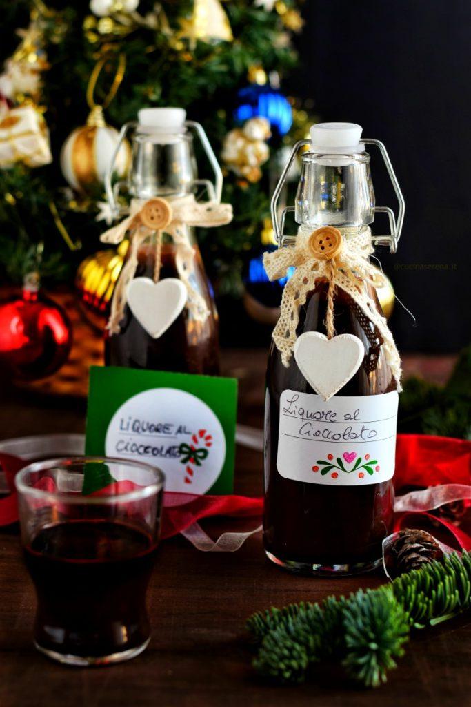 bottigliette decorate ripiene di liquore al cioccolato, sullo sfondo l'albero di natale, sul tavolo di legno decorazioni di nastri rami di abete etichette natalizie per regali homemade con scritto liquore al cioccolato oltre a un bicchierino con il liquore al cioccolato
