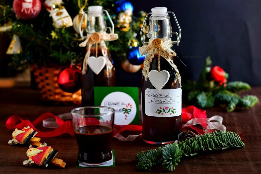 due bottigliette di liquore a cioccolato messe sfalzate una accanto all'altra davanti un bicchierino contenente il liquore  sul retro albero di natale con palline e sul tavolo due piccole mollette con babbo natale attaccato nastri e deocrazioni di albero di pino