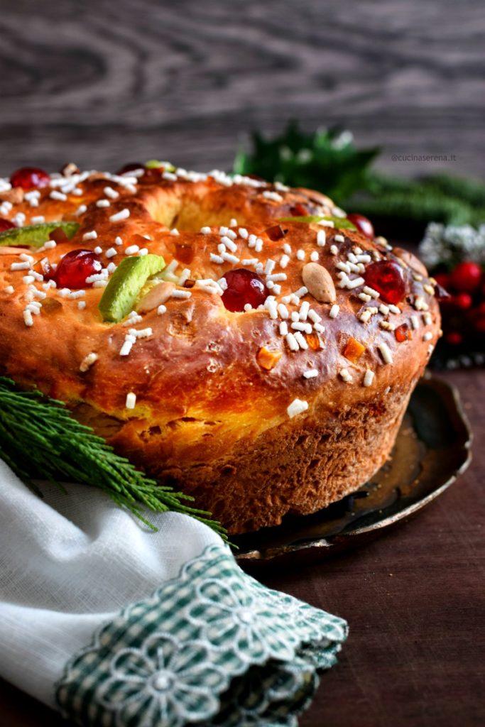 dolce dell'epifania spagnolo ciambella con frutta candita mandorle e granelle di zucchero messa su un vassoio appoggiato au un tavolo, intorno decorazioni di rami di abete e foglie di vischio