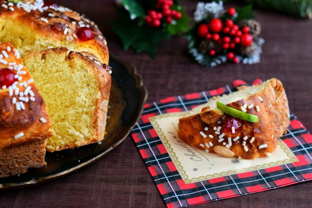 Fetta di ciambella Rescon de Reyes dolce lievitato spagnolo decorato con ciliege, cedro e arance candite, mandorle e granella di zucchero messa su un tovagliolino natalizio. A sinistra su un vassoio si intravede metà della ciambella tagliata con un altra fetta accostata al dolce intero