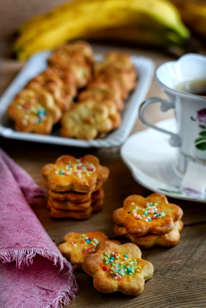 biscotti a forma di fiore decorati con diavolini, (ovvero confettini colorati) impilati uno sugli altri. Tre file di 3 e due biscotti impilati e altri due di poco sovrapposti sul tavolo. sullo sfondo un vassoio pieno di biscotto, due tazze da te e sulla sinistra un tovagliolo rosa di lino sfrangiato