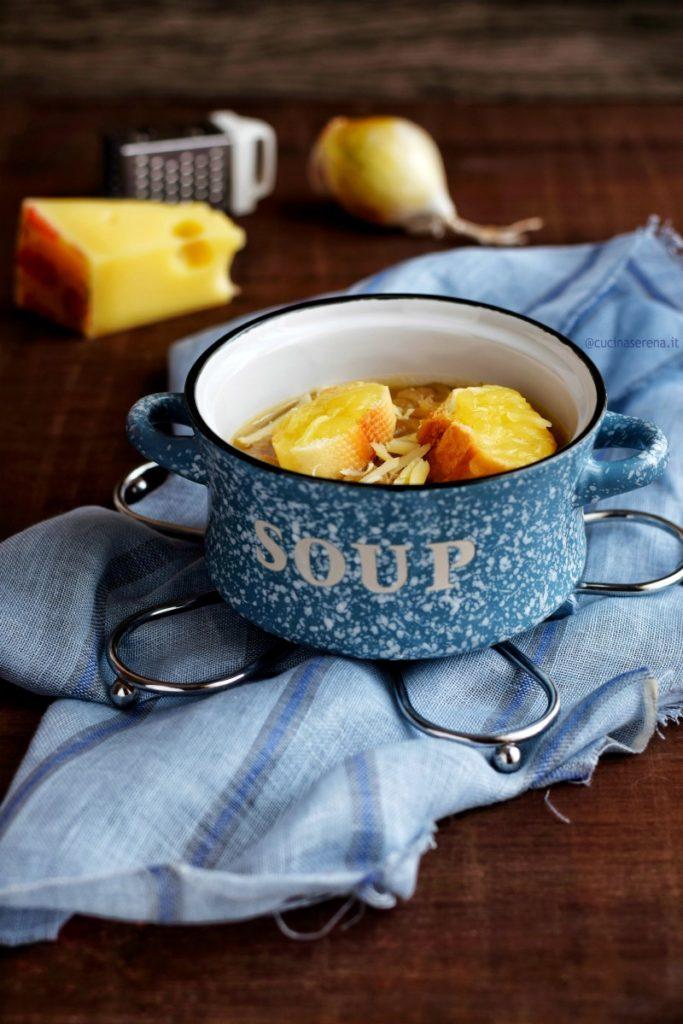 Zuppiera con soupe à l'oignon, zuppa di cipolle francese, e crostini di pane con formaggio groviera gratinati messa su telo azzurro posto sopra una tavola di legno scuro. Sullo sfondo gli ingredienti che richiamano la zuppa ovvero una cipolla bianca e la groviera oltre a una piccola grattugia usata per grattugiare il formaggio da spargere sui crostini e sulla zuppa