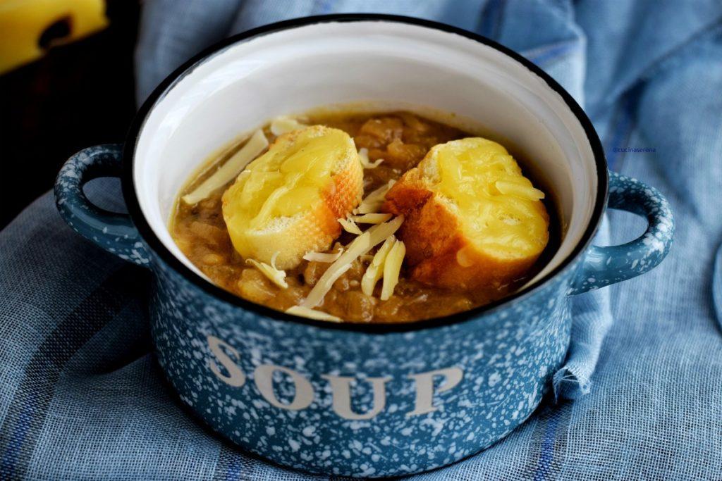 Soupe à l'oignon - zuppa di cipolle  francese in un pentolino celeste maculato fuori con una scritta bianca SOUP e smaltato all'interno bianco con bordi neri. Nel pentolino c'è la zuppa di cipolle due fette di baguette abbrustolite con groviera fusa sopra e scaglie di groviera per decorare. La zuppa viene infornata con i crostini prima di essere servita in modo che il formaggio si fonda