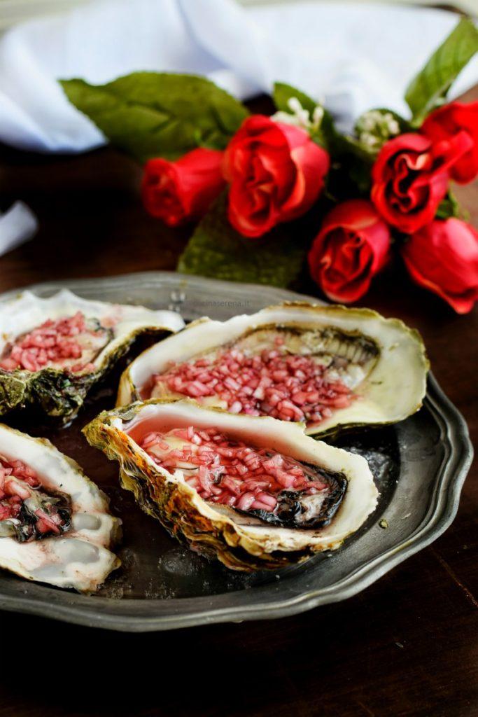 Ostriche condite con dressing mignonette fatto con scalogno, vino, aceto e pepe. Le ostriche sono adagiate su un vassoio in peltro con ghiaccio tritato, sullo sfondo un mazzo di rose e un drappo bianco di tela