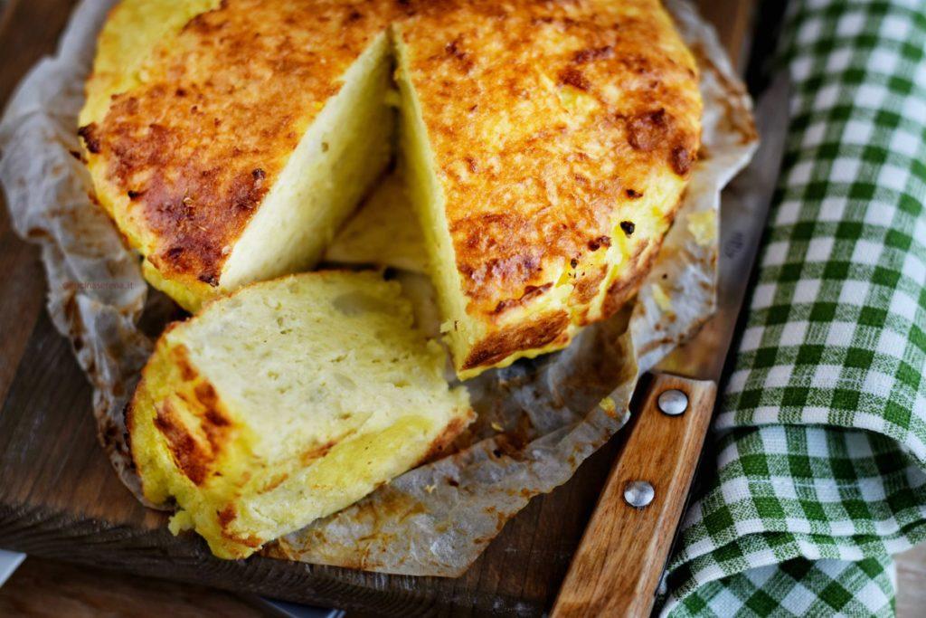 Rafanata lucana è una sorta di frittata a base di rafano. Nella foto è adagiata su carta forno con una fetta tagliate, sotto un tagliere in legno e uno strofinaccio a quadretti verdi