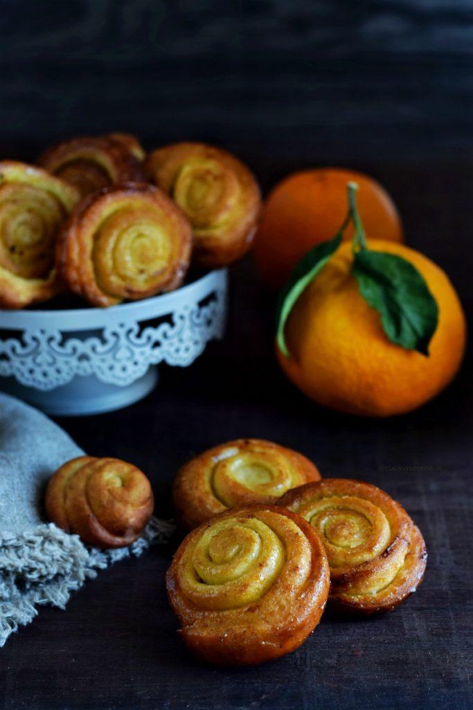 Arancini di carnevale, frittelle con zucchero e scorza di arancia fritte. Nella foto alcune sono su un'alzatina con accanto due arance, in primo piano ce ne sono tre appoggiate le une accanto alle altre