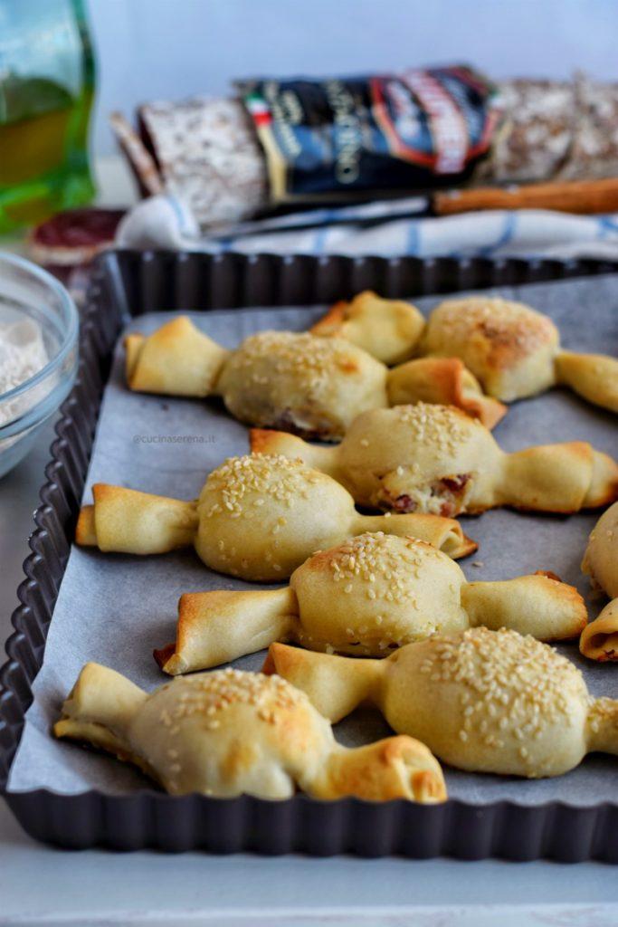 Antipasto a base di pasta matta ripiena si ricotta e salame a forma di caramella con decorazione di semi di sesamo sulla superficie