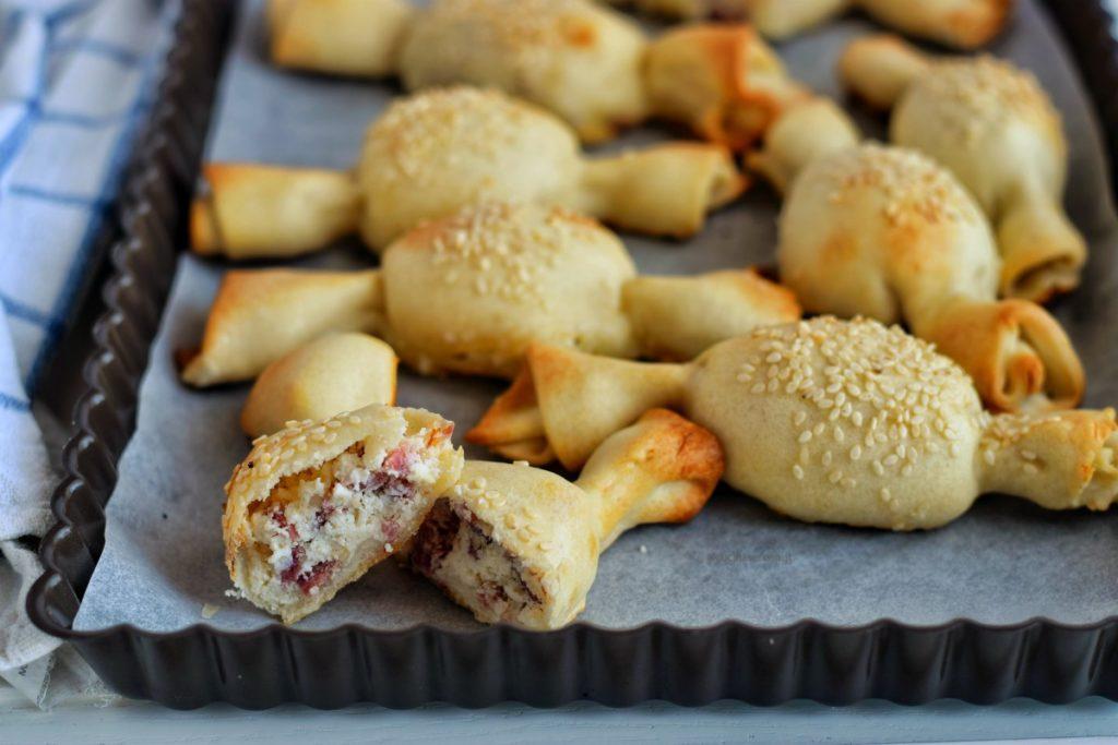 Caramelle di pasta matta tagliata in due con ripieno di ricotta e salame visibile. Sullo sfondo altre caramelle di pasa matta intere su una teglia da forno