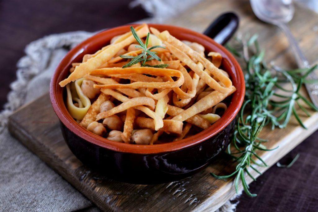 Ciceri e tria ricetta salentina servita un ciotola di coccio con manico, adagiata su un tagliere rustico sotto un telo grezzo. Il paiatto presenta la tipica pasta fritta oltre a quella cotta nella zuppa di ceci