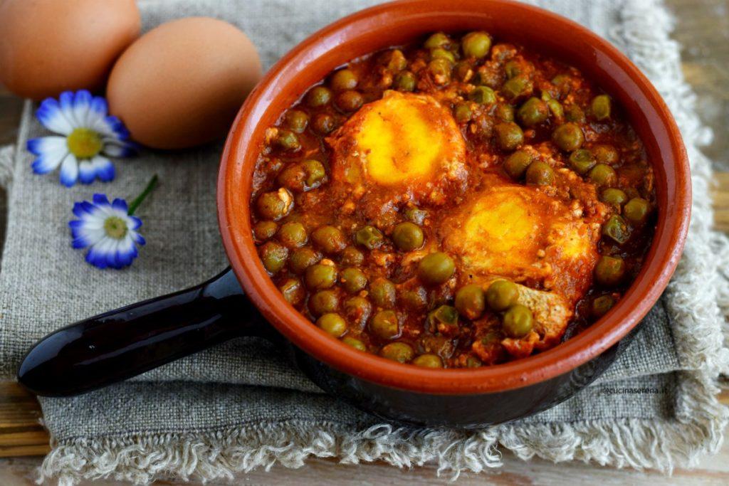 Uova con piselli al sugo: si tratta di uova cotte in un sugo di piselli in un tegamino di coccio. Sullo sfondo si intravedono le uova