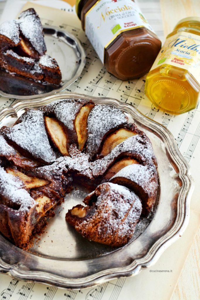 Dolce al cioccolato fatto con crema di nocciola nell'impasto e pere glassate al miele. Nella foto il dolce è su un vassoio di alluminio con alcune fette tagliate di cui una bene in evidenza, sotto il vassoio uno spartito musicale