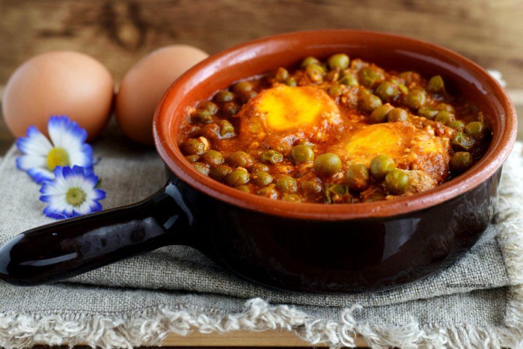 Uova con pisello al sugo è una ricetta facile e veloce con le uova e i legumi. La foto rappresenta un tegamino di coccio con manico nel quale ci sono le uova cotte immerse nei piselli al sugo