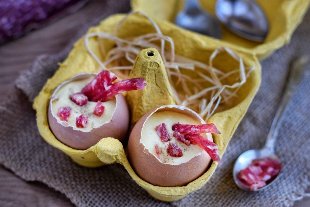 Crema inglese salata a base di panna e parmigiano servita nel guscio di uovo sterilizzato e completato con pezzetti di salame