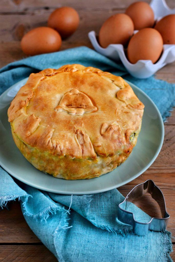 La torta pasqualina, torta salata fatta con diversi strati di pasta che racchiudino un ripieno di erbette ricotta e uova sode. Nella foto la torta chiusa anche sopra ha un decoro a forma di campanella. E' presentata in un piatto sotto al quale c'è un tovagliolo di lino sfrnagiato sullo sfondo si intravedono delle uova