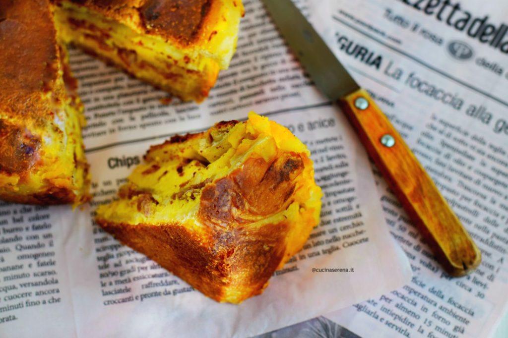 nella foto una fetta tagliata della pizza chiena, adagiata su un foglio di giornale. Poco dietro si intravede la torta rustica con una parte mancante e sulla destra un coltello
