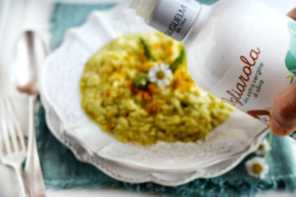 Nell'immagin si vede una mano che brandisce la bottiglia inclinata per mettere l'olio, sul piatto di risotto asparagi  e arancia che si intravede sotto - Olio Guglielmi
