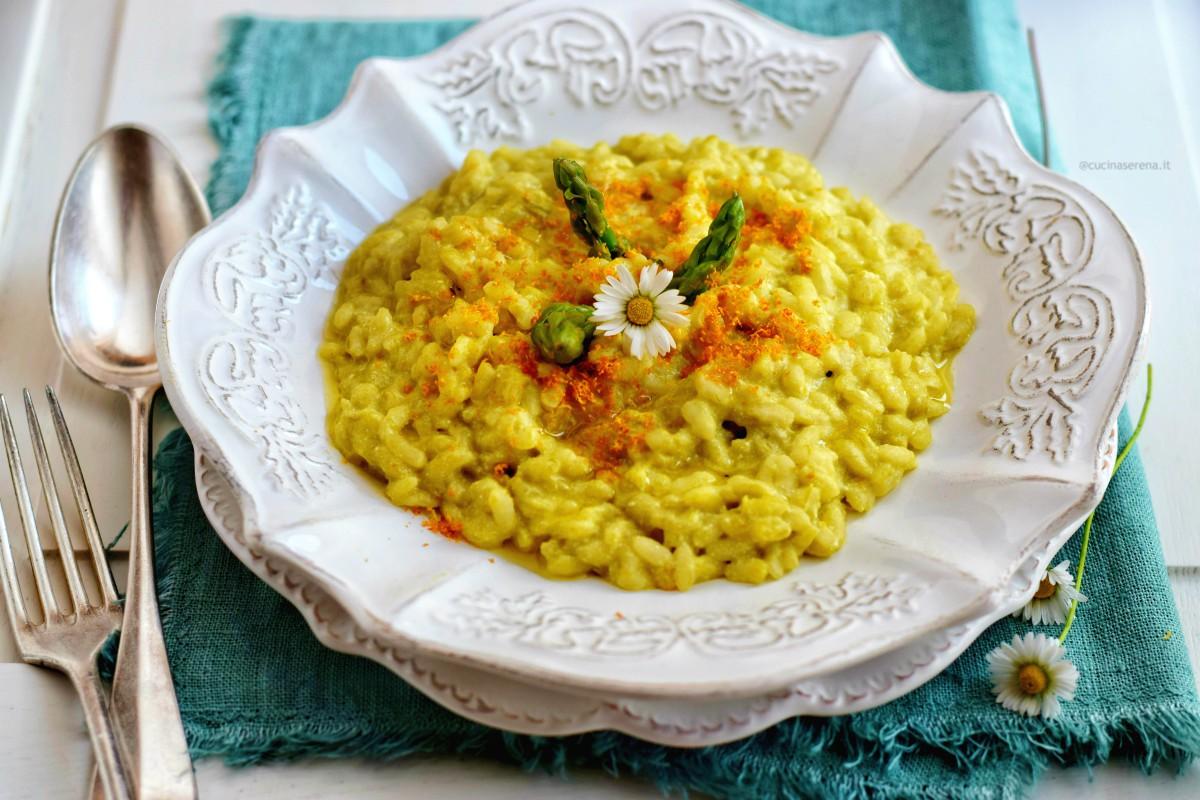 Risotto asparago e arancia servito su un piatto bianco serigrafato, sotto al quale c'è un sottopiatto adagiato su un tovagliolo verde di lino, a sinistra cucchiaio e forchetta