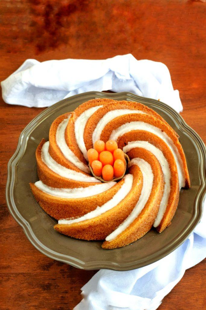 bundt cake carote, zucchina e polvere di liquirizia presentata su un alzatina al centro della ciambella con foro un mazzetto di carotine baby legate da uno spago