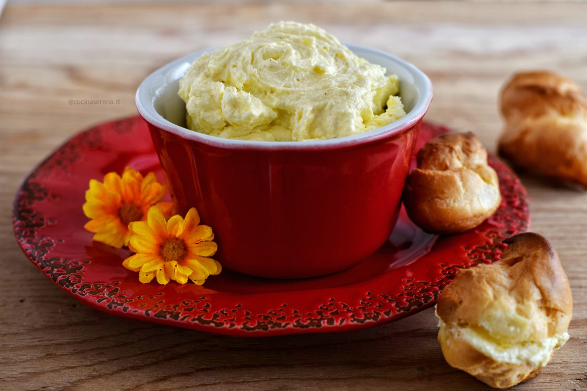 crema mousseline servita in un ciotola rossa con un sottopiatto in tinta dello stesso colore accanto dei bignè farciti di crema e altri vuoti