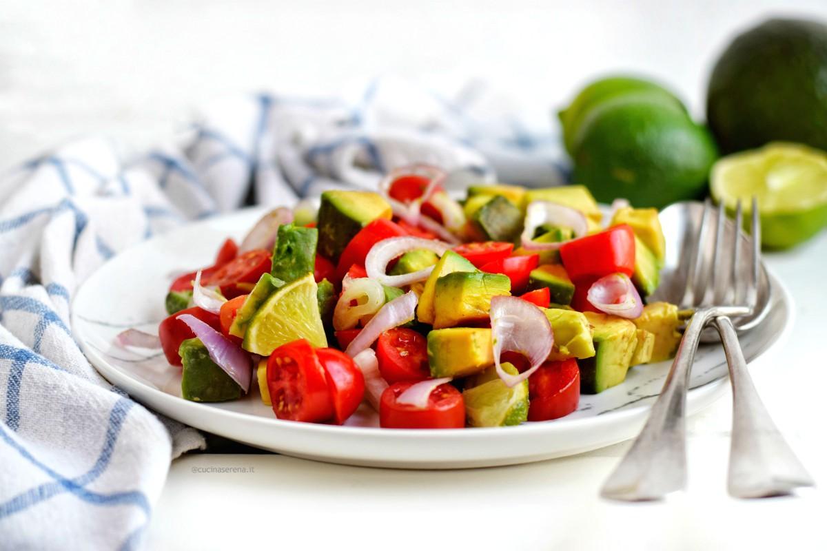 Insalata guacamole servits su un piatto marmorizzato accanto un canovaccio a scacchi bianco e blu sullo sfondo lime ad avocado