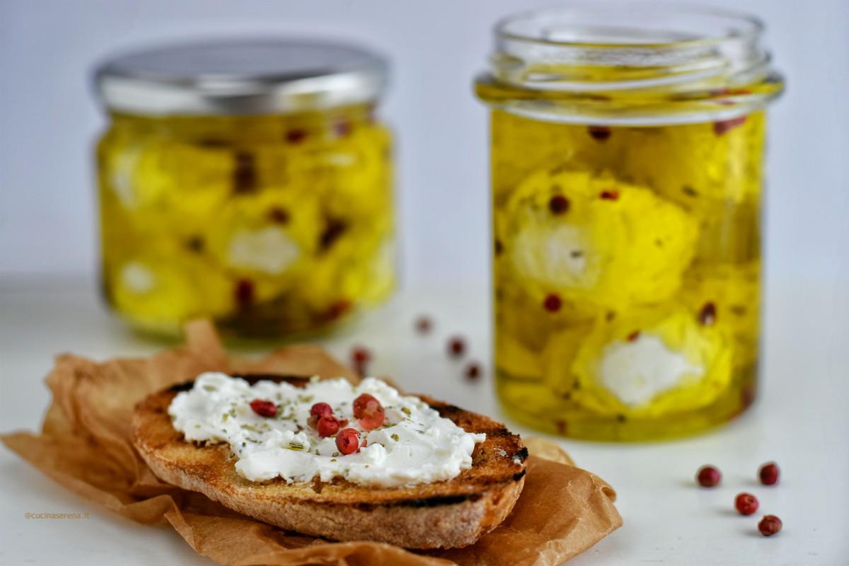 Labneh formaggio libanese fatto con yogurt filtrato, in questa foto ridotto in palline e messo nei barattoletti con spezie e pepe rosa in grani. di lato una fetta di pane con il formaggio spalmato