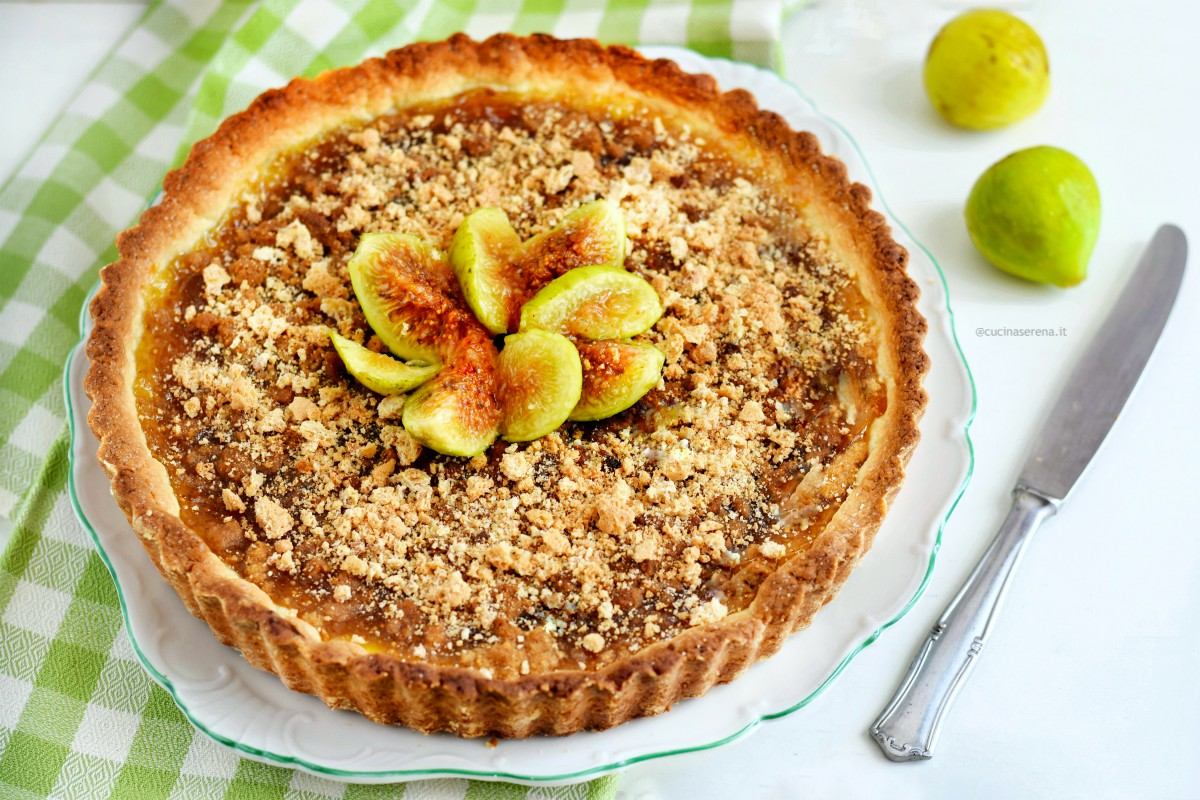 Figues jam crust with amaretti cookies - the crust in in a dish on the table a knife and two fresh figues fruit