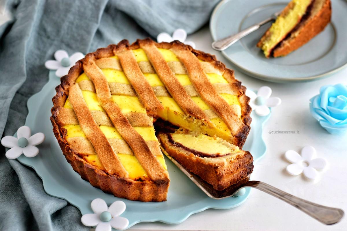 Crostata ricotta e visciole rivisita con crema di ricotta allo zafferano e pasta frolla al caffè. Nella foto dolce nel vassoio con una fetta tagliata adagiata sulla paletta per torte