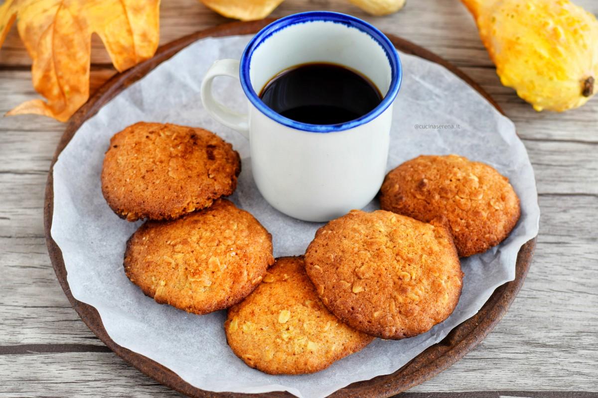 biscotti morbidi alla zucca, nocciole e avena nella foto presentati in un vassoio con una tazza di caffè bianca sull sfondo i simboli dell'autunno: foglie e zucca