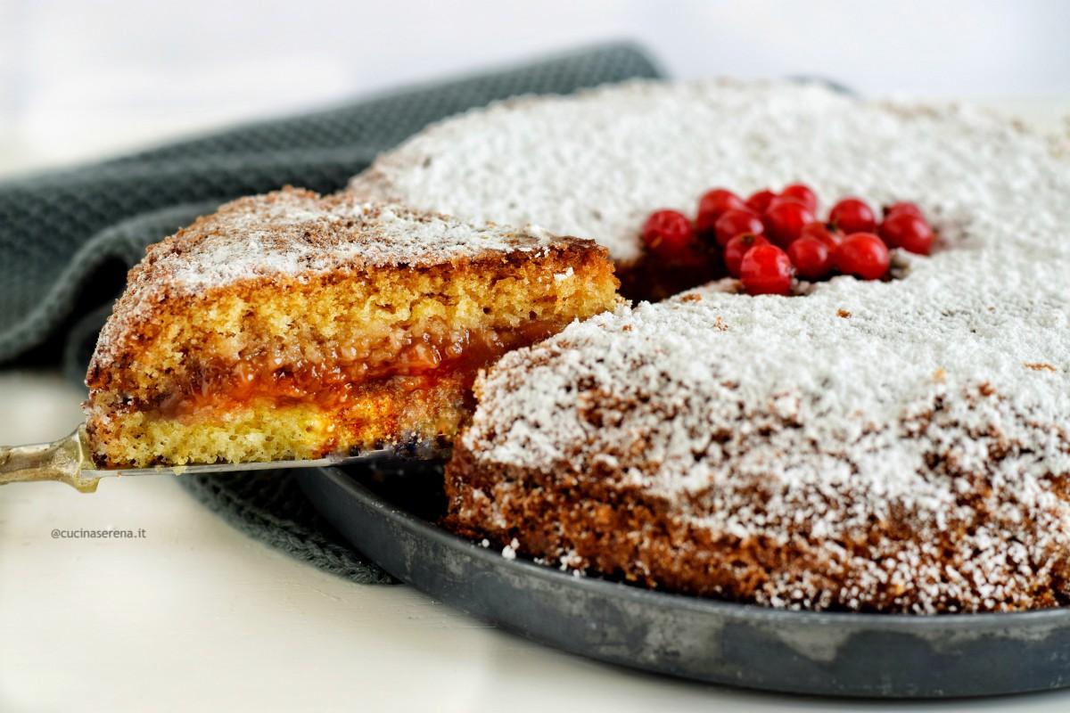 Fetta di torta versata con confettura di fragole e fragoline di bosco.