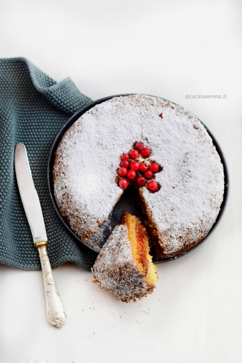 Torta versata posta in una vassoio vintage con una fetta tagliata rivolta verso l'alto in cui si vede il ripieno di confettura della torta - (foto zenitale)