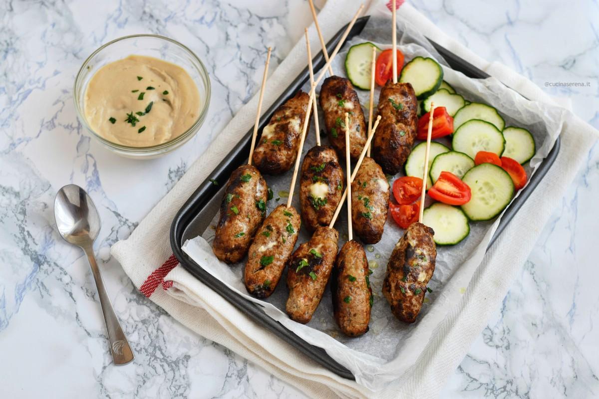 Kofta polpette di carne medio orientali con carne macinate e spezie nella foto servita nella versione  kofta meshweya come spiedini in una teglia con salsa tahini in accompagnamento