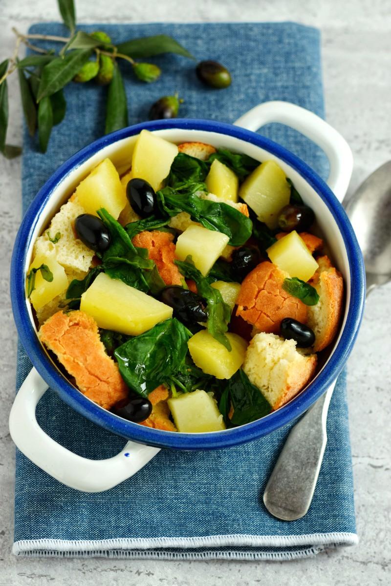 Pancotto garganico fatto con patate , rucola e olive nella foto servito in una ciotola bianca di latta con bordi blu, sullo sfondo un ramoscello di ulivo con olive