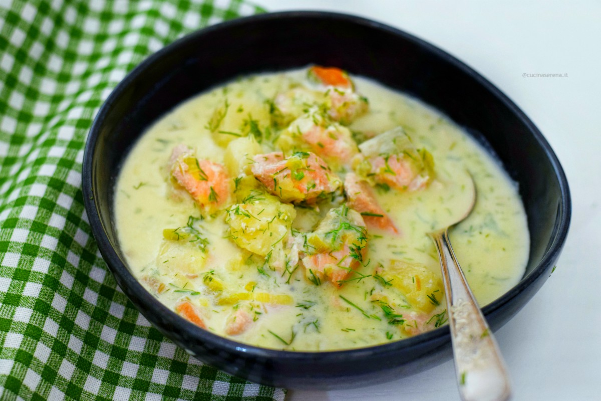 salmon soup with carrots, potatoes, fresh cream, salmon and dill served in a blu soup plate