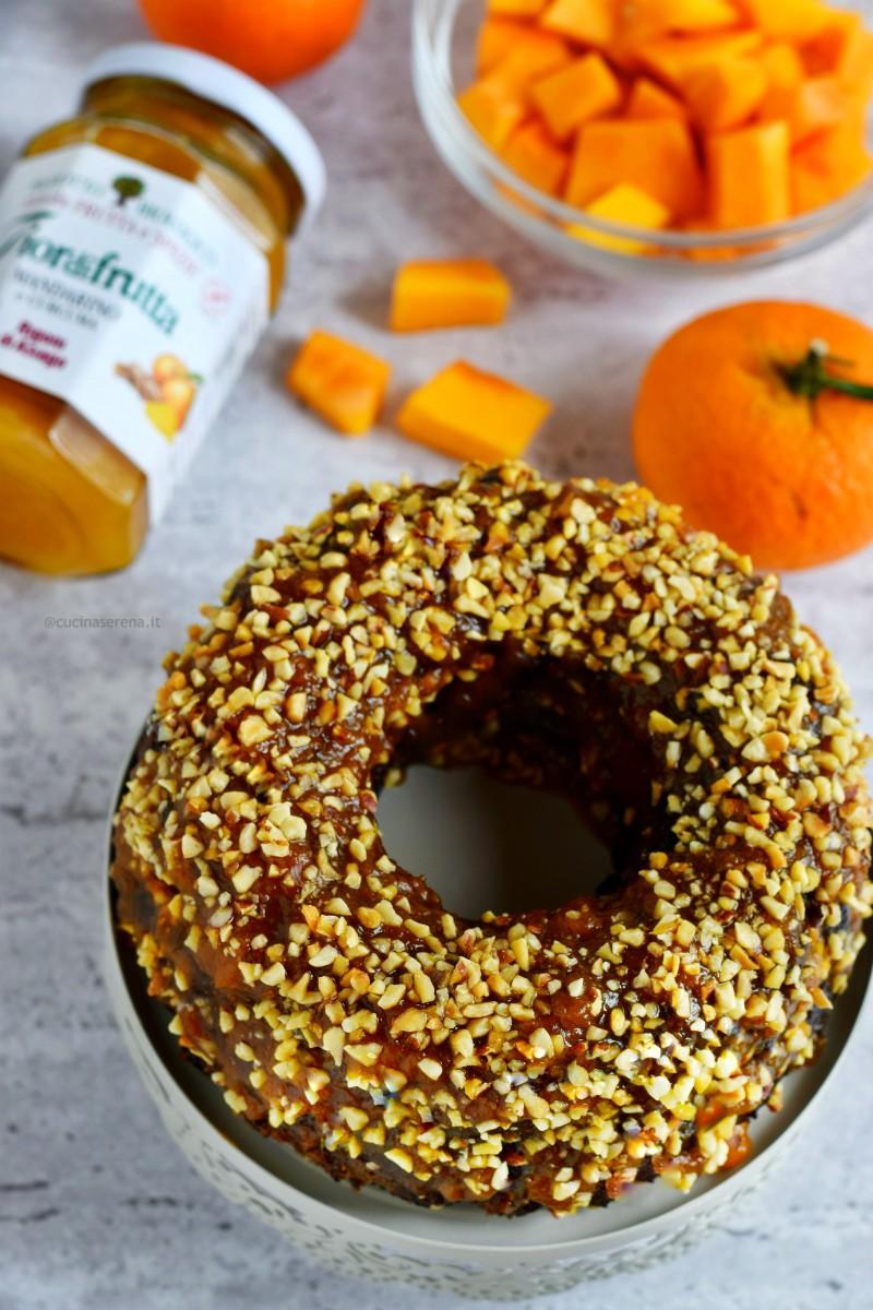 Torta alla zucca e mandarino con curcuma gluten free. Nella foto zenitale il dolce è adagiato su una alzatina per dolci e sullo sfondo si intravedono mandarini e zucca a cubetti