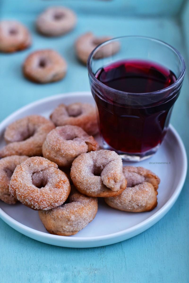 ciambellie  al vino rosso nella foto presentate in um piatto con accanto un bicchiere di vino rosso