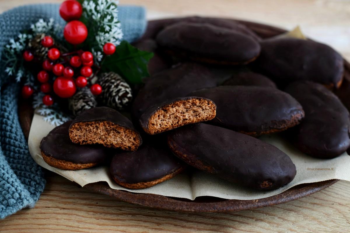 Susumelle dolce di pasta morbida speziato con miele glassato al cioccolato fondente. Nella foto presentato su un piatto vintage color ruggine un biscotto è spezzato e si vede l'interno.