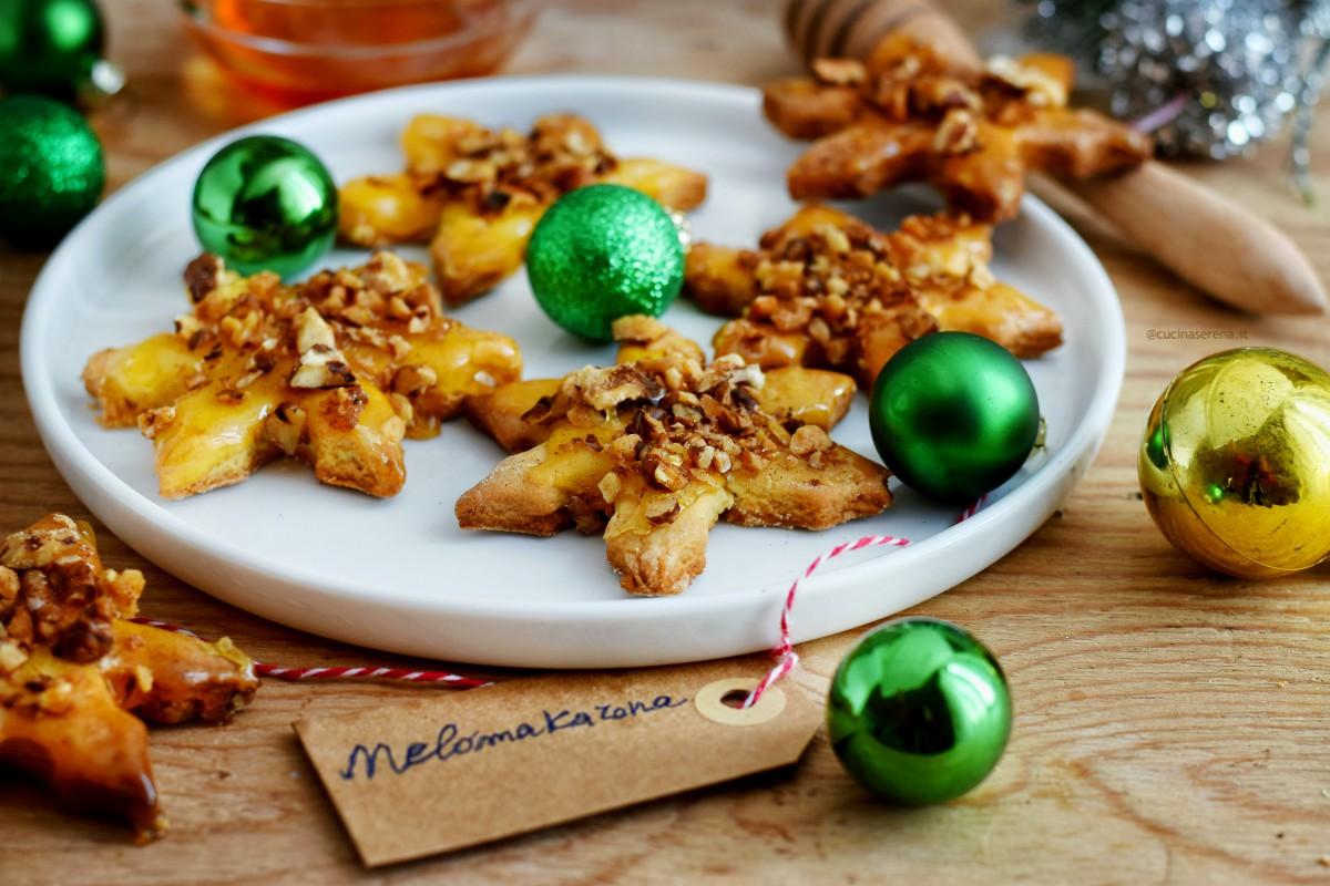 melamakarona biscotti natalizi greci, nella foto presentati in un piatto a forma di stella con decorazioni natalizie attorno