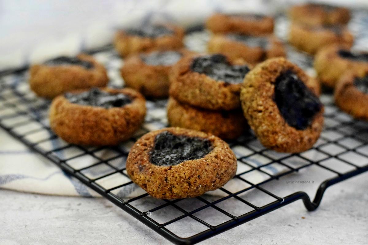 biscotti senza uova farciti con confettura di mirtilli neri, nella foto sono disposti su una gratella forata messa sopra un canovaccio