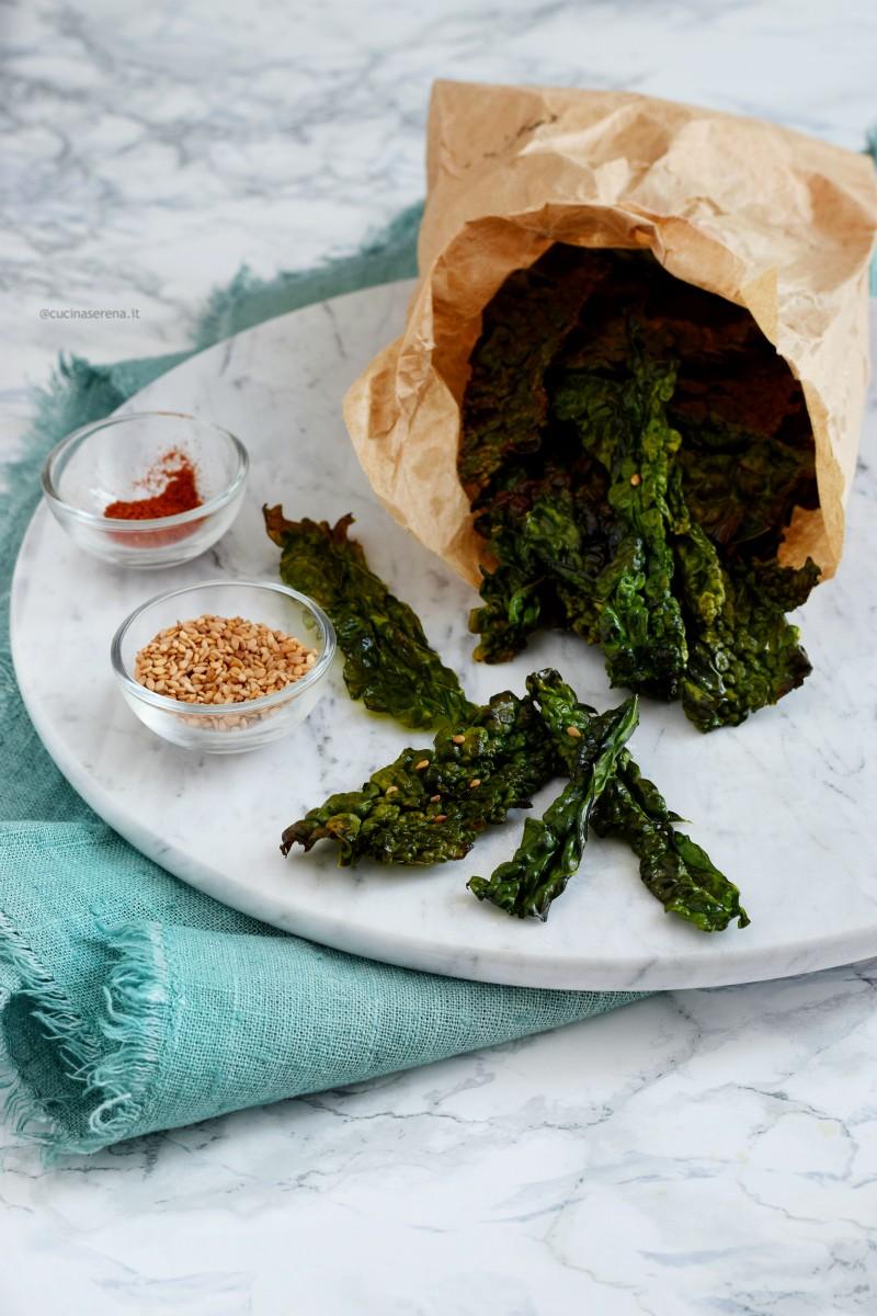 Chips di cavolo nero - kale chips al forno servite come snack in un sacchetto di carta alimentare come fossero patatine -