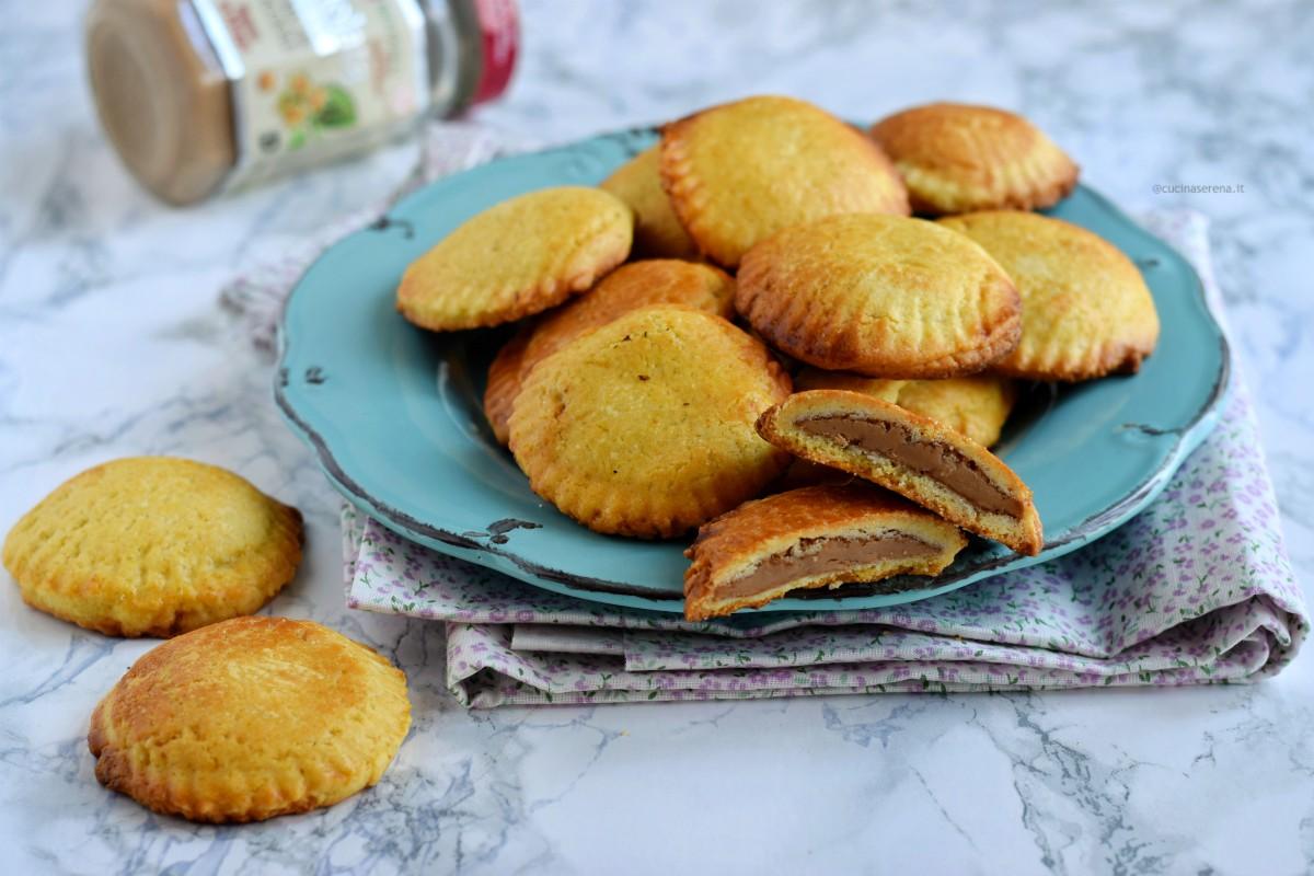 Ravioli dolci a forma di conchiglia di pasta frolla farciti con crema di nocciole bianca Rigoni di Asiago nella foto presentati in un piatto azzurro, uno dei quali aperto per vedere l'interno