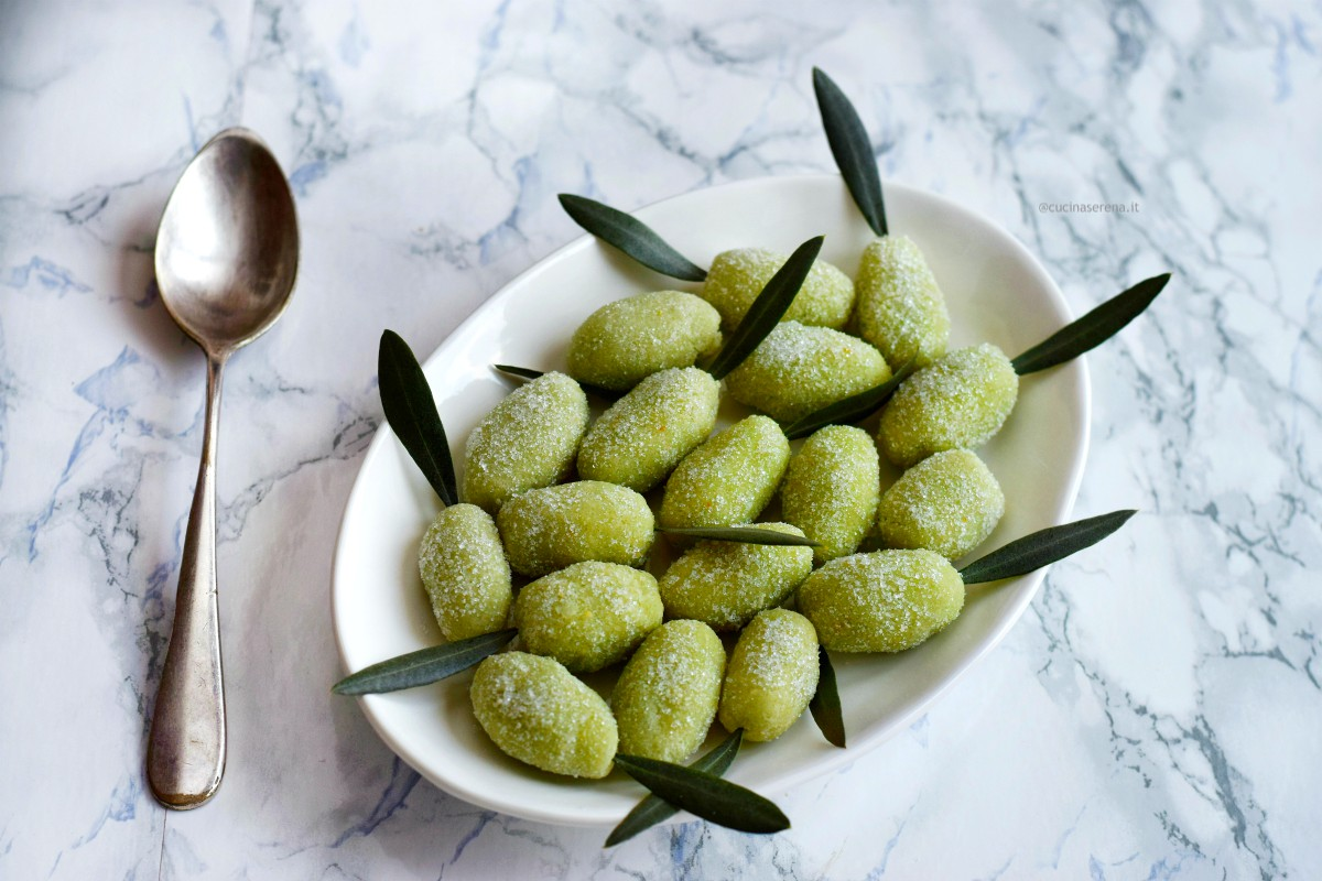 olivette in pasta di mandorel nella foto servite in un piatto bianco con foglie di ulivo come decorazione e un cucchiaio per prenderle accanto al piatto