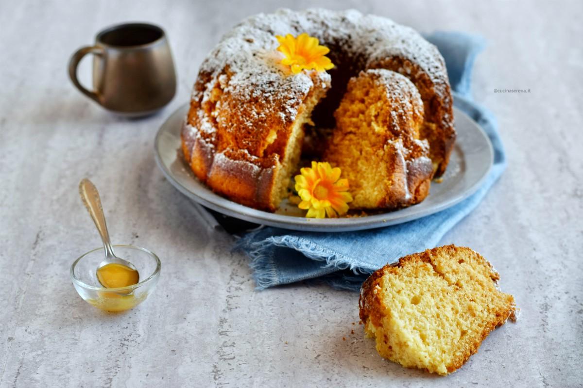 Dolce soffice al latte e miele nella foto una fetta tagliata adagiata sul tavolo e sullo sfondo il dolce affettato e il miele in una ciotolina con un cucchiaino dentro